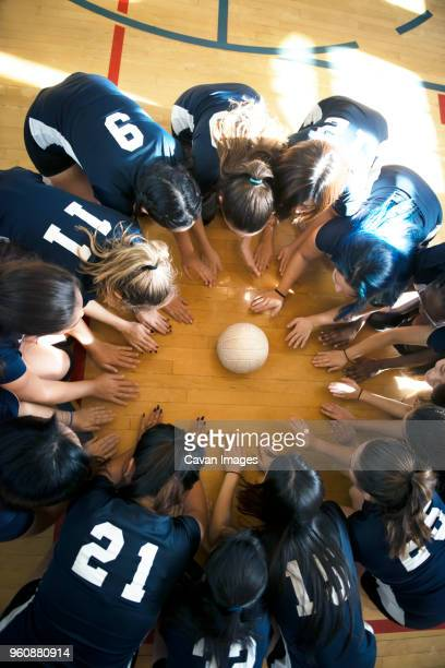 high angle view of girls volleyball team huddling on floor - volleyball mannschaftssport stock-fotos und bilder