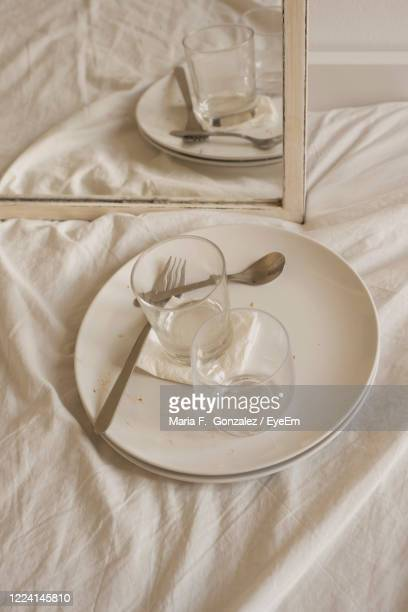high angle view of glasses and plates on bed - lentezza foto e immagini stock