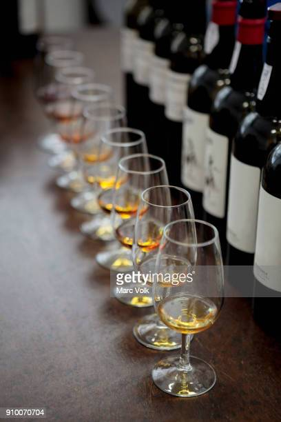 High angle view of glasses with Madeira wine by bottles on bar counter