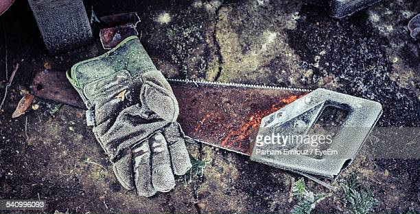 high angle view of glove and hand saw - parham emrouz stock pictures, royalty-free photos & images