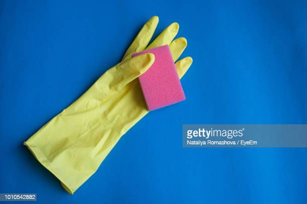 high angle view of glove and sponge on table - washing up glove stock pictures, royalty-free photos & images