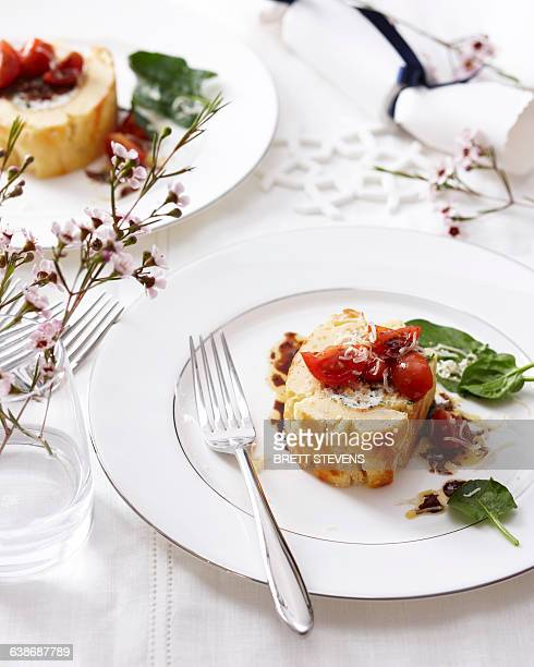 High angle view of goat cheese roulade with tomatoes and basil on elegant plate