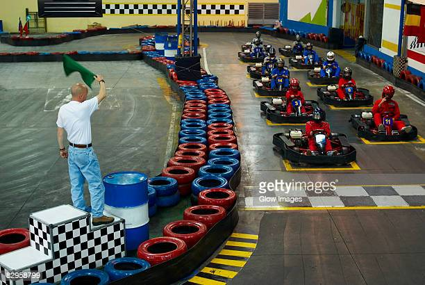 High angle view of go-cart racer at starting line with a man waving a flag