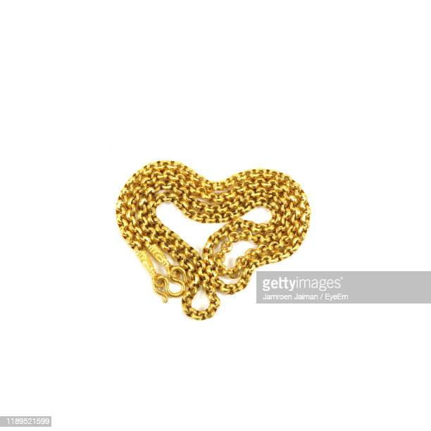 high angle view of gold chain necklace on white background - gold chain necklace stock pictures, royalty-free photos & images