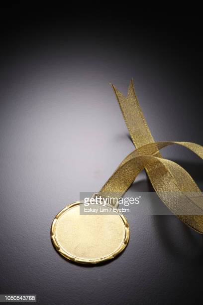 high angle view of gold medal on gray table - médaille d'or photos et images de collection