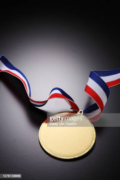 high angle view of gold medal on gray table - gold medal stock pictures, royalty-free photos & images