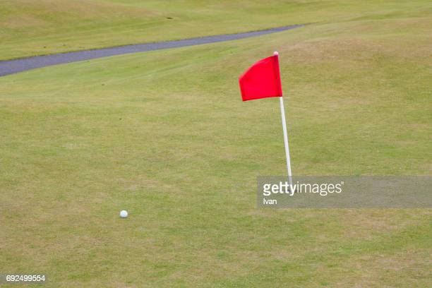 high angle view of golf ball by flag on grass, st andrews golf course, scotland, uk - golf flag stock photos and pictures