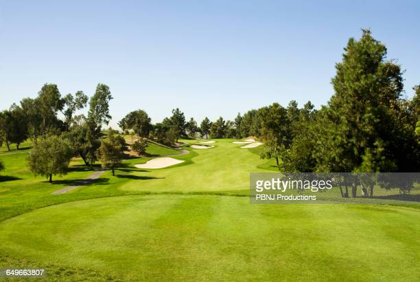 High angle view of golf course under blue sky
