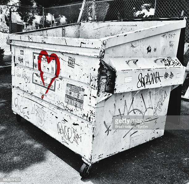 High Angle View Of Graffiti On Dumpster By Fence On Field