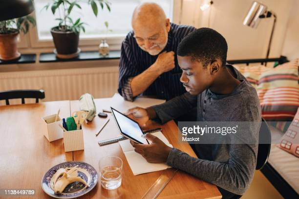 high angle view of grandfather looking at grandson doing research over digital tablet at table in living room - african american man helping elderly stock pictures, royalty-free photos & images