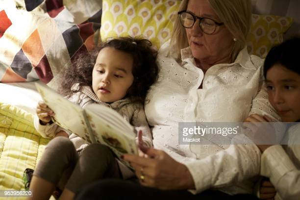 high angle view of grandmother reading book to granddaughters while lying on bed at home - storytelling stock pictures, royalty-free photos & images