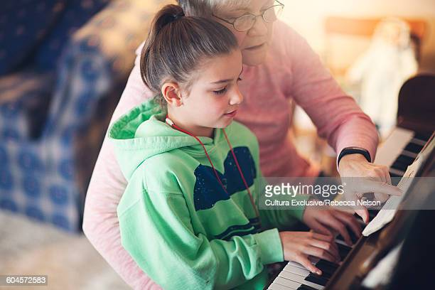 High angle view of grandmother teaching granddaughter to play piano