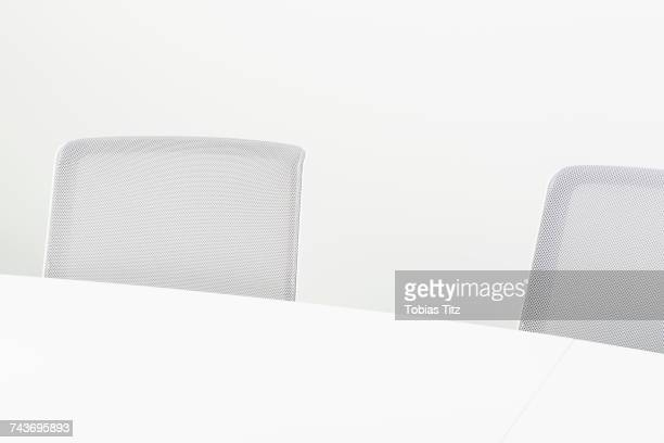 High angle view of gray office chairs by table against white background