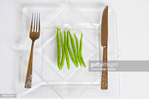 high angle view of green beans in glass plate with fork and table knife - bush bean stock photos and pictures