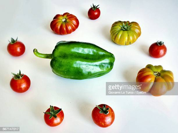 high angle view of green bell pepper amongst tomatoes against white background - green bell pepper stock pictures, royalty-free photos & images
