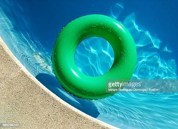 high angle view of green inflatable ring in swimming pool - tube stock pictures, royalty-free photos & images