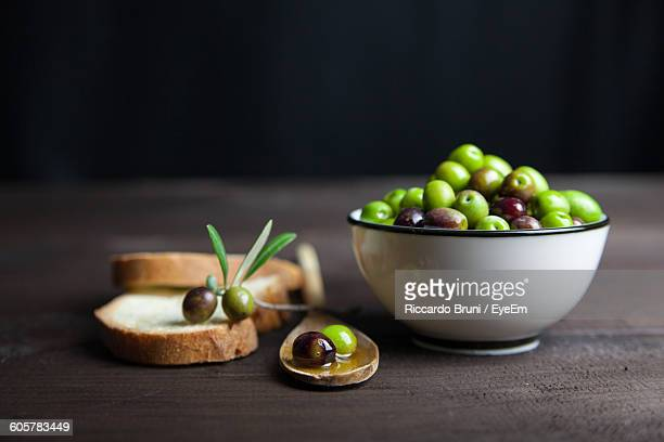 high angle view of green olives and bread on table - aceitunas fotografías e imágenes de stock