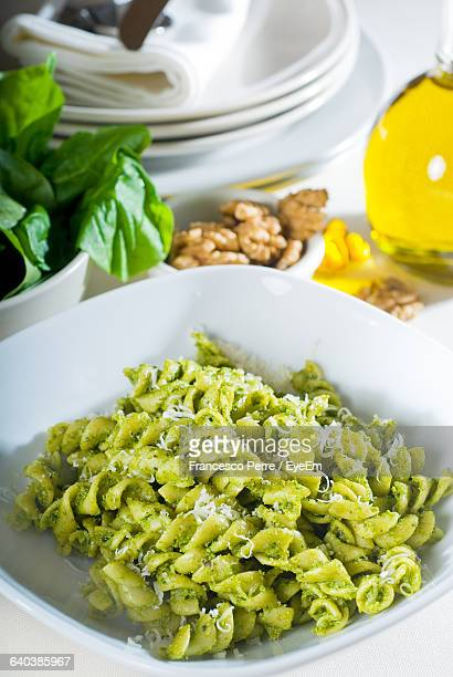 High Angle View Of Green Pasta Served In Bowl On Table