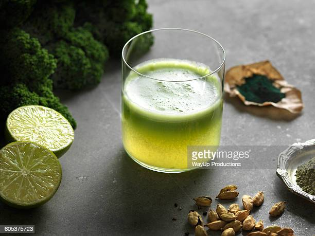 High angle view of green raw juice with halved lime and nutritional supplement