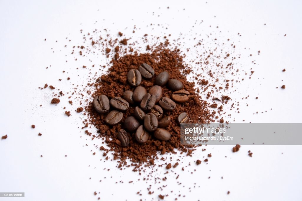 High Angle View Of Ground Coffee And Beans Over White Background : Stock Photo