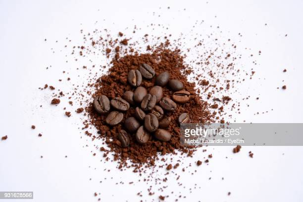 high angle view of ground coffee and beans over white background - café moulu photos et images de collection