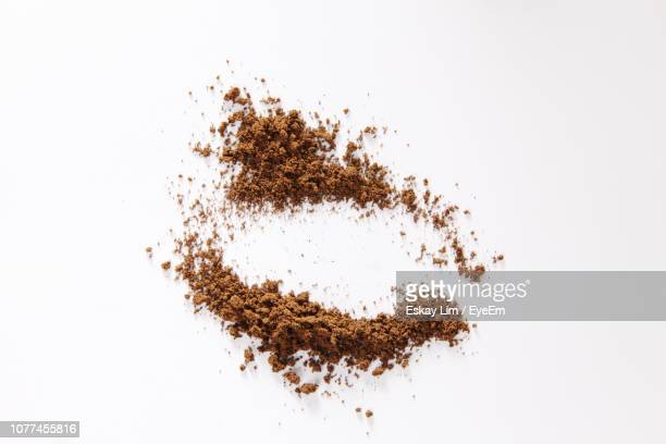 high angle view of ground coffee over white background - café moulu photos et images de collection