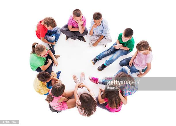 High angle view of group of children playing whispering game.