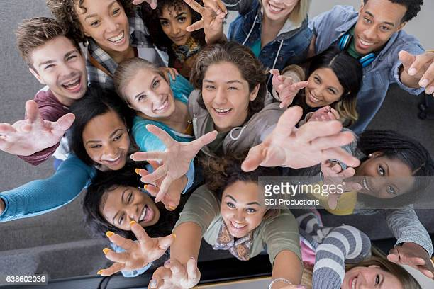 High angle view of group of college students reaching up