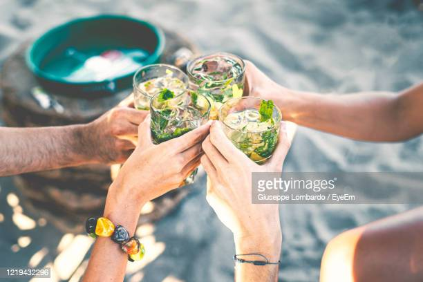 high angle view of group of people toasting holding glass with tropical  cocktails - celebratory toast stock pictures, royalty-free photos & images