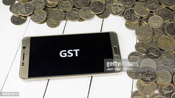 High Angle View Of Gst In Smart Phone By Coins On Table
