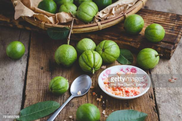 high angle view of guavas in basket by salt in bowl at table - guava fruit stock photos and pictures