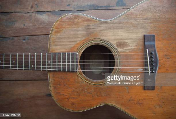 high angle view of guitar on wooden table - musical instrument string stock pictures, royalty-free photos & images
