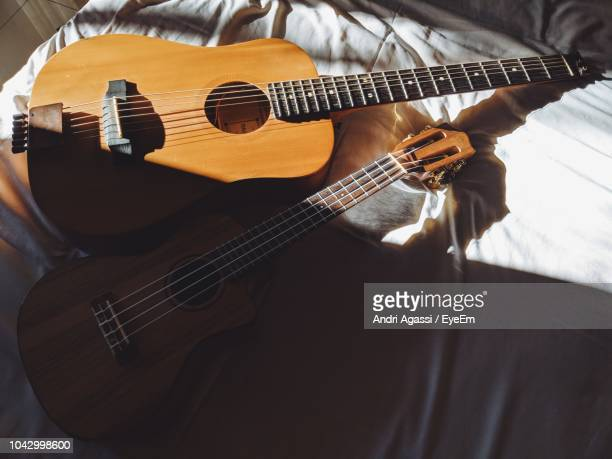High Angle View Of Guitars On Bed