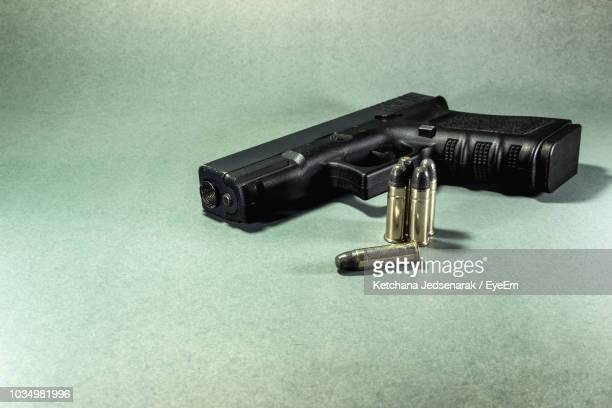high angle view of gun on green background - pistolet photos et images de collection