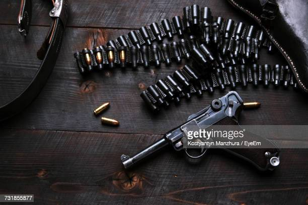 High Angle View Of Gun With Bullets On Wooden Table