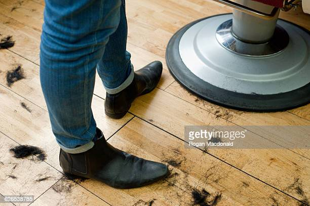 High angle view of hairdressers legs and hair cuttings on wooden floor