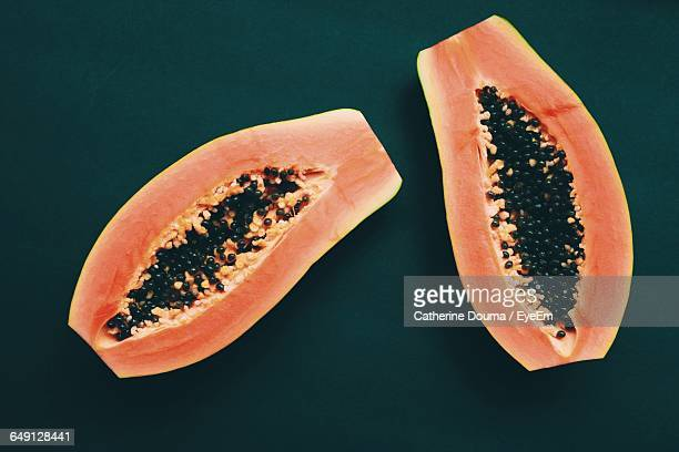 high angle view of halved papaya against green background - papaya stock photos and pictures