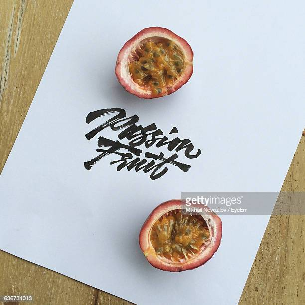 High Angle View Of Halved Passion Fruit With Paper On Table