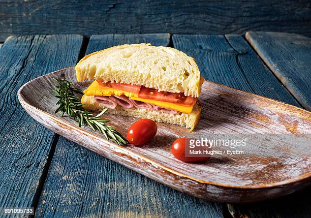 High Angle View Of Ham Sandwich With Tomatoes And Rosemary In Tray