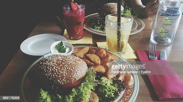 High Angle View Of Hamburger And Fried Potatoes With Caipirinha Cocktail On Table