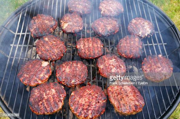 High Angle View Of Hamburgers On Barbecue Grill In Back Yard