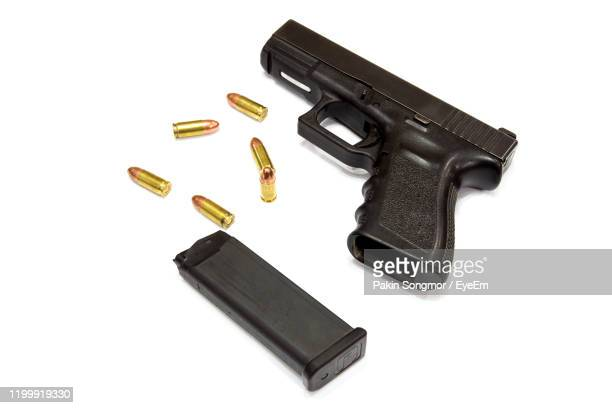 high angle view of hand gun and bullets against white background - pistol stock pictures, royalty-free photos & images