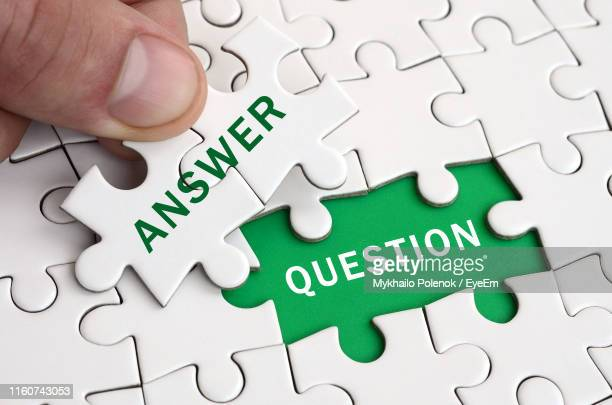 high angle view of hand holding jigsaw pieces with text over puzzle - q&a stock pictures, royalty-free photos & images