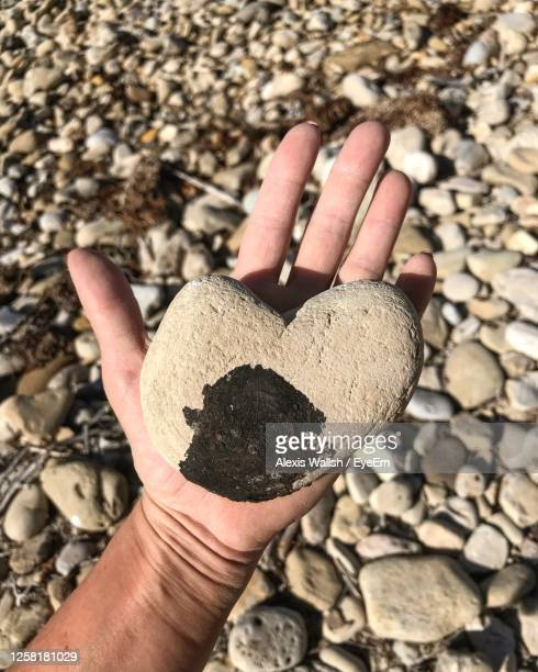 high angle view of hand holding pebbles - rancho palos verdes stock pictures, royalty-free photos & images