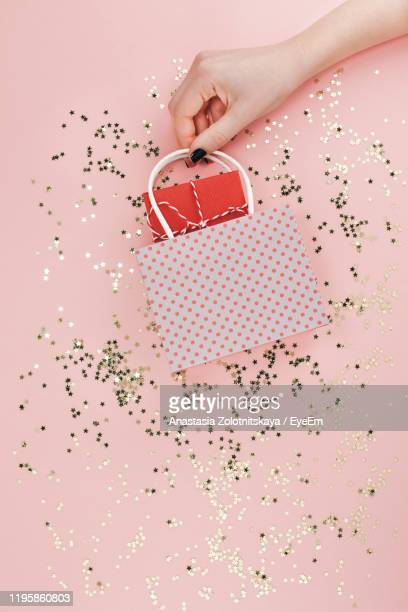 high angle view of hand holding shopping bag over sequins against pink background - スパンコール ストックフォトと画像