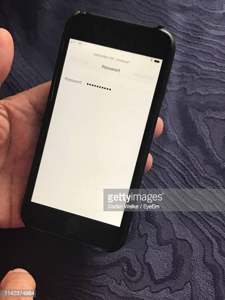 high angle view of hand holding smart phone with password screen on table - password stock pictures, royalty-free photos & images