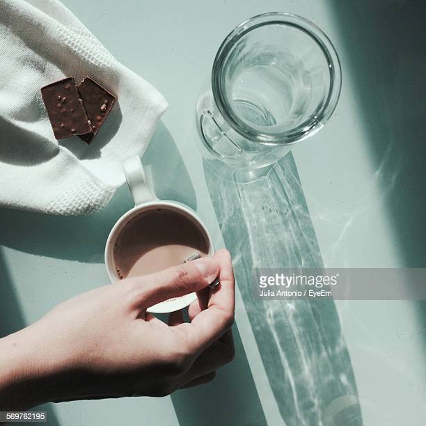 High Angle View Of Hand Holding Spoon In Coffee At Table