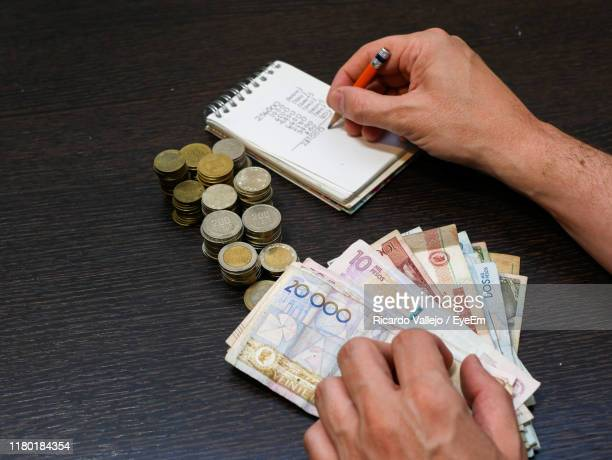 high angle view of hand writing in book by coins and paper currency on table - dinero fotografías e imágenes de stock