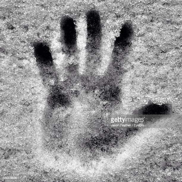 High Angle View Of Handprint On Snowcapped Land