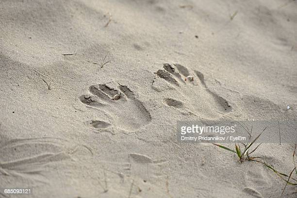 high angle view of handprints and wedding rings on sand at beach - his and hers stock pictures, royalty-free photos & images